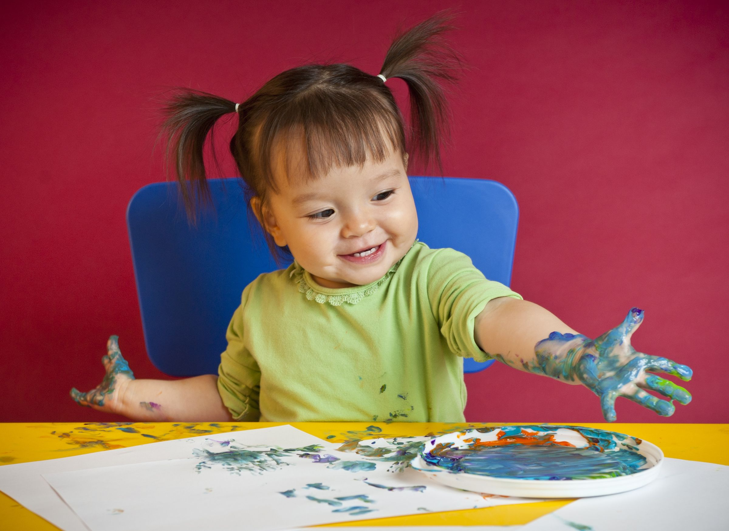 12599788 - little happy girl discovering finger painting